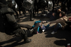 Riot Police remove housing rights activists as they tries to stop Luisa Gracia Gonzalez and her family's eviction and the demolition of their house by a forced expropriation in Madrid, Spain, Friday, Feb. 27, 2015. Madrid authorities say 11 people were arrested after several dozen protesters clashed with police who were carrying out an eviction order. A city spokeswoman said seven people were arrested for throwing gasoline at police officers, though she said the fuel was not set alight. The official spoke on condition of anonymity in keeping with city hall rules. Evictions in Spain have soared since the country's economic crisis began in 2008 and increasing numbers of people were unable to meet mortgage payments. Protesters regularly try to prevent evictions, but Friday's clash was particularly tense after a campaign to keep the family in its home. The house was expropriated for demolition as part of new urban project. Some 30 protesters tried to stop it, accusing authorities of real estate speculation.(AP Photo/Andres Kudacki)