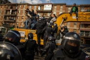 Riot Police remove a housing rights activists who claimed a bulldozer as they triy to stop Luisa Gracia Gonzalez and her family's eviction and the demolition of their house by a forced expropriation in Madrid, Spain, Friday, Feb. 27, 2015. Madrid authorities say 11 people were arrested after several dozen protesters clashed with police who were carrying out an eviction order. A city spokeswoman said seven people were arrested for throwing gasoline at police officers, though she said the fuel was not set alight. The official spoke on condition of anonymity in keeping with city hall rules. Evictions in Spain have soared since the country's economic crisis began in 2008 and increasing numbers of people were unable to meet mortgage payments. Protesters regularly try to prevent evictions, but Friday's clash was particularly tense after a campaign to keep the family in its home. The house was expropriated for demolition as part of new urban project. Some 30 protesters tried to stop it, accusing authorities of real estate speculation.(AP Photo/Andres Kudacki)