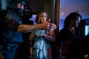 Carmen Rives, 50, centre, gestures as riot police enter her apartment to evict her in Madrid, Spain, Tuesday, June 2, 2015. The unemployed woman lost her foreclosed apartment to a moneylender because she could not afford the pay her debt due to her financial situation. The eviction was carried out by dozens of riot police who arrested at least 12 anti-eviction activists. (AP Photo/Andres Kudacki)