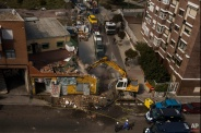 A bulldozer demolish, police stand guard and workers remove furniture during Luisa Gracia Gonzalez and her family during eviction and the demolition of their house by a forced expropriation in Madrid, Spain, Friday, Feb. 27, 2015. Madrid authorities say 11 people were arrested after several dozen protesters clashed with police who were carrying out an eviction order. A city spokeswoman said seven people were arrested for throwing gasoline at police officers, though she said the fuel was not set alight. The official spoke on condition of anonymity in keeping with city hall rules. Evictions in Spain have soared since the country's economic crisis began in 2008 and increasing numbers of people were unable to meet mortgage payments. Protesters regularly try to prevent evictions, but Friday's clash was particularly tense after a campaign to keep the family in its home. The house was expropriated for demolition as part of new urban project. Some 30 protesters tried to stop it, accusing authorities of real estate speculation. (AP Photo/Andres Kudacki)