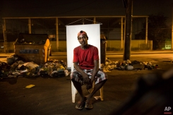 """In this March 14, 2015 photo, Andre Oliveira, 32, poses for a portrait in an open-air crack cocaine market, known as a """"cracolandia"""" or crackland, where users can buy crack, and smoke it in plain sight, day or night, in Rio de Janeiro, Brazil. Andre makes a living by collecting discarded, recyclable items on the streets. (AP Photo/Felipe Dana)"""