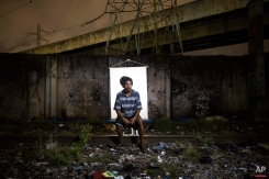 """In this March 18, 2015 photo, Douglas Wallace, 26, poses for a portrait in an open-air crack cocaine market, known as a """"cracolandia"""" or crackland, where users can buy crack, and smoke it in plain sight, day or night, in Rio de Janeiro, Brazil. Collectively, the estimated 1 million crack users in Brazil are a frightening blight that's deeply troubling to government officials, whose programs have done little to halt the drug's march across the nation. Some recent studies have shown that Brazil now consumes more crack than any other country.(AP Photo/Felipe Dana)"""