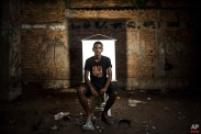 """In this March 17, 2015 photo, Anderson Pereira, 23, poses for a portrait in an open-air crack cocaine market, known as a """"cracolandia"""" or crackland, where users can buy crack, and smoke it in plain sight, day or night, in Rio de Janeiro, Brazil. Pereira wears a T-shirt with a message that reads in Portuguese; """"Nothing should seem natural."""" (AP Photo/Felipe Dana)"""