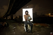 """In this March 17, 2015 photo, Renato Dias, 39, writes in his notebook as he poses for a portrait in an open-air crack cocaine market, known as a """"cracolandia"""" or crackland, where users can buy crack, and smoke it in plain sight, day or night, in Rio de Janeiro, Brazil. Dias, who has been using crack for about 4 years, says he uses his notebook as a form of distraction. He writes about super heroes and dreams of becoming one. (AP Photo/Felipe Dana)"""