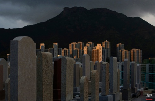 In overcrowded Hong Kong both the living and dead are facing a shortage of space. In tightly-packed city the dead are causing a problem for the living. In this Thursday, Nov. 19, 2015. photo, graves cover a hillside next to apartment buildings at a cemetery in the Kowloon City district of Hong Kong, where both the living and dead are facing a shortage of space. (AP Photo/Kin Cheung)