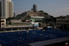 In this Saturday, Nov. 28, 2015 photo, graves cover a hillside next to football pitch and apartment buildings in the Kowloon City district of Hong Kong, where both the living and dead are facing a shortage of space. In tightly-packed Hong Kong, the dead are causing a problem for the living. (AP Photo/Kin Cheung)