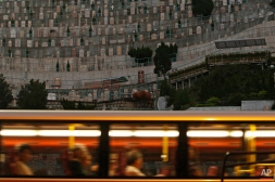 In this Thursday, Nov. 19, 2015 photo, a bus drives passes a cemetery in the Kowloon City district of Hong Kong, where both the living and dead are facing a shortage of space. In tightly-packed Hong Kong, the dead are causing a problem for the living. (AP Photo/Kin Cheung)