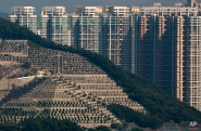 In this Sunday, Nov. 22, 2015 photo, graves cover a hillside in front of apartment buildings in Hong Kong, where both the living and dead are facing a shortage of space. (AP Photo/Kin Cheung)