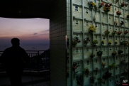 In this Sunday, Nov. 22 photo, A man walks past a wall of niches for cremated remains in the background at a public columbarium in Hong Kong. In tightly-packed Hong Kong, the dead are causing a problem for the living. (AP Photo/Kin Cheung)