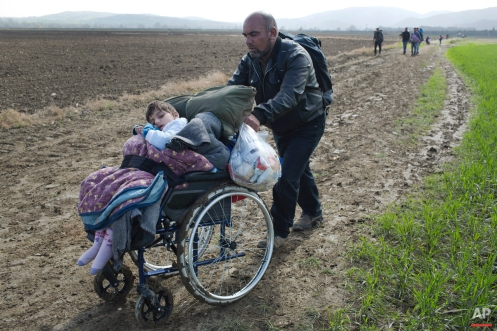 In this Tuesday, March 1, 2016 photo, Hamo from Iraq pushes a wheelchair with his 8-year old disabled daughter Sidra through fields in their effort to arrive at the Greek border station of Idomeni. The fields of Idomeni were never a proper border crossing between Greece and Macedonia. It's where the freight trains cross, and earlier in the crisis refugees and migrants traveling clandestinely through the Balkans used it as they followed the tracks _ on foot _ north toward central Europe. Soon it became a major staging point in the biggest mass movement of people the continent has seen since vast displaced populations were being repatriated in the bloody aftermath of World War II. (AP Photo/Petros Giannakouris)