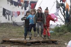 Refugee children jump on a muddy mattress in a makeshift camp at the northern Greek border post of Idomeni, Greece, Friday, March 18, 2016. (AP Photo/Boris Grdanoski)