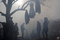 Migrants gather around fire and dry clothes at the northern Greek border station of Idomeni, Tuesday, March 8, 2016. (AP Photo/Visar Kryeziu)