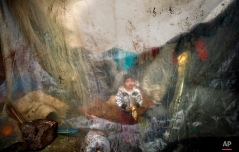 A migrant child sits behind plastic sheets covering tents during a rainfall in a makeshift camp at the northern Greek border post of Idomeni, Greece, Tuesday, March 15, 2016. (AP Photo/Vadim Ghirda)