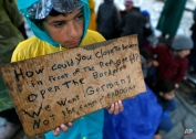 A migrant boy shows a banner saying he wants to travel to Germany rather than camps set up by Turkish President Erdogan, during a protest demanding the opening of the border between Greece and Macedonia in the northern Greek border station of Idomeni, Greece, Wednesday, March 23, 2016. (AP Photo/Darko Vojinovic)