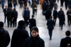 A security officer, center bottom, stands guard on the steps of the Great Hall of the People as delegates leave after a plenary session of the National People's Congress (NPC) in Beijing, China, Wednesday, March 9, 2016. (AP Photo/Mark Schiefelbein)