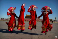 Chinese bus ushers leap as they pose for a photograph at Tiananmen Square during a plenary session of the National People's Congress (NPC) at the Great Hall of the People in Beijing, Sunday, March 13, 2016. (AP Photo/Mark Schiefelbein)
