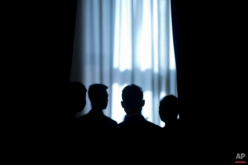 Security personnel stand in front of a curtain inside the Great Hall of the People during a plenary session of the National People's Congress (NPC) in Beijing, Sunday, March 13, 2016. (AP Photo/Mark Schiefelbein)