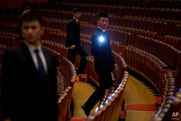 A security officer shines a flashlight as he walks through a seating area after the closing session of the Chinese People's Political Consultative Conference (CPPCC) at the Great Hall of the People in Beijing, Monday, March 14, 2016. (AP Photo/Mark Schiefelbein)