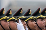 In this Monday, March 21, 2016, photo, Chinese People's Liberation Army soldier adjusts a hat of a member of an honor guard as they prepare for a welcome ceremony for visiting German President Joachim Gauck, outside the Great Hall of the People in Beijing. (AP Photo/Andy Wong)