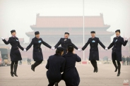 Hostesses, who facilitated the transportation of delegates arriving by bus, pose for photos on Tiananmen Square near the Great Hall of the People in Beijing during a meeting ahead of Saturday's opening session of China's National People's Congress (NPC), Friday, March 4, 2016. (AP Photo/Mark Schiefelbein)