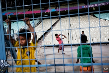 Family members of ground staff at the Eden Gardens play a game of cricket on the sidelines as Pakistani cricket team practices at the ground during ICC World Twenty20 2016 tournament in Kolkata, India, Friday, March 18, 2016. (AP Photo/Bernat Armangue)