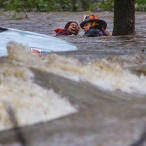Little Rock Fire Capt. Steve Kotch, right, and an unidentified woman stumble and fall into the water as Kotch uses a cable safety line to rescue her from her flooded car in Boyle Park in Little Rock, Ark., during heavy rainfall Wednesday, March 30, 2016. Lightning and heavy rains hit central Arkansas during the evening rush hour. (Stephen B. Thornton/The Arkansas Democrat-Gazette via AP)