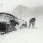 Lisa Rose tries dig her car out of a parking lot in Monument, Colo., Wednesday, March 23, 2016. A powerful spring blizzard stranded travelers at Denver's airport and shut down hundreds of miles of highway in Colorado, Wyoming and Nebraska as it spread into the Midwest on Wednesday. (Jerilee Bennett/The Gazette via AP)