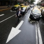 In this April 15, 2016 photo, a man walks past taxi drivers blocking an avenue to protest Uber in downtown Buenos Aires, Argentina. Taxi drivers paralyzed parts of Buenos Aires during rush hour against Uber launching its service in Argentina's capital city in defiance of local authorities. (AP Photo/Victor R. Caivano)