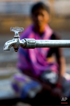 In this May 10, 2016, photo, a woman waits to fill water from a municipal water tap whose supply is provided by the Jaldoot water train in Latur, in the Indian state of Maharashtra. (AP Photo/Manish Swarup)
