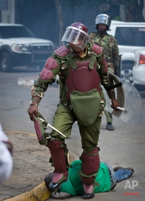 In this photo taken Monday, May 16, 2016, a Kenyan riot policeman walks away after repeatedly kicking a protester as he lies in the street after falling down while trying to flee from them, during a protest in downtown Nairobi, Kenya. In an incident that has stirred anger and condemnation across Kenya, a policeman is seen beating and kicking one protester who had fallen on a road curb, while the U.S. and human rights activists have condemned violence by Kenyan police at the opposition protest for election reforms. (AP Photo/Ben Curtis)