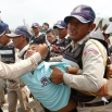 A Worker Union member, Suth Chet, 36, center, is grabbed by district security personnel during a protest rally at a blocked street near the National Assembly, in Phnom Penh, Cambodia, Monday, April 4, 2016. More than a hundred workers on Monday staged a rally near the National Assembly to call on lawmakers not to create legal union, according to a union leader. (AP Photo/Heng Sinith)