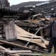 Tokio Miyamoto examines the damage of houses collapsed by earthquakes in Aso, Kumamoto prefecture, Japan, Sunday, April 17, 2016. Two nights of increasingly terrifying earthquakes flattened houses and triggered major landslides in southern Japan. (AP Photo/Shizuo Kambayashi)
