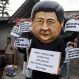 A Tibetan activist wears a mask in the likeness of the Chinese president Xi Jinxing during a street protest in Dharmsala, India, Friday, April 1, 2016. Exiles claim that three Tibetans were arrested in eastern Tibet on Wednesday for discussing the recent Tibetan elections in exile on social media in Tibet. (AP Photo/Ashwini Bhatia)