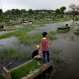 Indonesian youth stand on a grave as they fish at a cemetery inundated by floodwaters after a heavy downpour caused a nearby river to burst its banks in Jakarta, Indonesia, Thursday, April 21, 2016. (AP Photo/Tatan Syuflana)