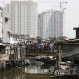 Residents gather on a bridge during an eviction in Jakarta, Indonesia, Monday, April 11, 2016. Hundreds of people were evicted from a section of government land as part of an effort to increase the percentage of open green spaces in the capital. (AP Photo/Achmad Ibrahim)