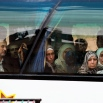 In this picture taken Thursday, April 14, 2016, Syrians look through a window after they loaded their belongings onto a bus in the town of Palmyra in the central Homs province, Syria. Thousands of residents of this ancient town who fled Islamic State rule are returning briefly to check on their homes and salvage what they can - some carpets, blankets, a fridge or a few family mementos. (AP Photo/Hassan Ammar)