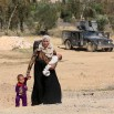 In this Monday, April 4, 2016 photo, a mother and her children flee their homes during clashes between Iraqi security forces and Islamic State group in Hit, 85 miles (140 kilometers) west of Baghdad. Families, many with small children and elderly relatives, say they walked for hours Monday through desert littered with roadside bombs to escape airstrikes and clashes. (AP Photo/Khalid Mohammed)