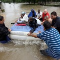 Residents use an air mattress to float on floodwaters as they evacuate their flooded apartment complex Monday, April 18, 2016, in Houston. Storms have dumped more than a foot of rain in the Houston area, flooding dozens of neighborhoods and forcing the closure of city offices and the suspension of public transit. (AP Photo/David J. Phillip)