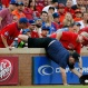 A fan leans over the wall and onto the field to glove a foul ball hit by Texas Rangers' Elvis Andrus in the first inning of a baseball game against the Houston Astros on Tuesday, April 19, 2016, in Arlington, Texas. (AP Photo/Tony Gutierrez)