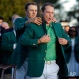 Defending champion Jordan Spieth, left, helps 2016 Masters champion Danny Willett, of England, put on his green jacket following the final round of the Masters golf tournament, Sunday, April 10, 2016, in Augusta, Ga. (AP Photo/Chris Carlson)