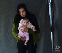 In this picture made on Thursday, May 12, 2016, 17-years-old Soumaya Zallaan, a Syrian mother from the city of Deir ez-Zor, poses with her baby girl Ritag in a tent made of blankets given by the UNCHR at the refugee camp of the northern Greek border point of Idomeni. Soumaya Zallaan is one of the dozens of refugee women that gave birth while stranded in Idomeni after the Greek- Macedonian border was closed in early March 2016. Ritag, the family's first child, was born on Wednesday, April 20, 2016 in the hospital of the nearby town of Policastro. The three member family wants to go to Germany. (AP Photo/Petros Giannakouris)