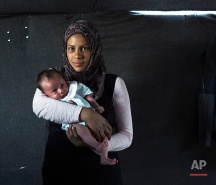 In this picture made on Thursday, May 12, 2016, 19-year-old Rajad Alhelo, a Syrian mother from the city of Deir ez-Zor, poses with her baby girl Yasmin in a tent made of blankets given by the UNCHR at the refugee camp of the northern Greek border point of Idomeni. Rajad Alhelo is one of the dozens of refugee women that gave birth while stranded in Idomeni after the Greek- Macedonian border was closed in early March 2016. Yasmin, the family's first child, was born on Friday, April 1, 2016 in the hospital of the nearby town of Kilkis. The three member family wants to go to Germany or any other safe place in central Europe. (AP Photo/Petros Giannakouris)