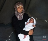In this picture made on Saturday, May 14, 2016, 19-year-old Farah Sheikh Ahmed, a Syrian mother from the city of Idlib, poses with her baby girl Maram in a tent made of blankets given by the UNCHR at the refugee camp of the northern Greek border point of Idomeni. Farah Sheikh Ahmed is one of the dozens of refugee women that gave birth while stranded in Idomeni after the Greek- Macedonian border was closed in early March 2016. Maram the family's first child, was born on Wednesday, April 20, 2016 in the hospital of the nearby town of Kilkis. The three member family wants to go to Germany. (AP Photo/Petros Giannakouris)