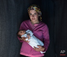 In this picture made on Friday, May 16, 2016, 23-year-old Rojin, a Kurdish-Syrian mother from the city of Qamishli, Syria, poses with her baby girl Beritan in a tent made of blankets given by the UNCHR at the refugee camp of the northern Greek border point of Idomeni. Rojin is one of the dozens of refugee women that gave birth while stranded in Idomeni after the Greek- Macedonian border was closed in early March 2016. Berating, the family's first child, was born on Sunday, April 10, 2016 in the hospital of the nearby town of Kilkis. The three member family wants to go to Switzerland. (AP Photo/Petros Giannakouris)