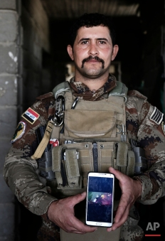 """In this Wednesday, June 8, 2016 photo, Sgt. Ahmed Abdelaziz, 29 of Iraq's elite counterterrorism forces shows an Islamic State video of his brother's death, at a battle position on the southern edge of Fallujah, Iraq. Abdelaziz, has been almost continually deployed fighting the Islamic State group ever since the militants overran nearly a third of Iraq in the summer of 2014. Now he's on the front lines of Fallujah, a city declared """"fully liberated"""" on Sunday, June 26, 2016 by the commander leading the fight against IS. Abdelaziz has with him what he always brings into battle: a photo of his brother. (AP Photo/Maya Alleruzzo)"""