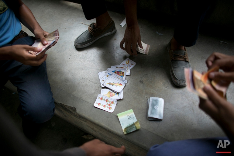 In this May 31, 2016 photo, boys gamble on a card game in the patio of their public high school in Caracas, Venezuela. As many as 40 percent of teachers skip class on any given day to wait in food lines, according to the Venezuela Teacher's Federation. The school director has asked nearby supermarkets to let teachers cut in line, and she's disciplined staff for selling students passing grades in exchange for scarce goods like milk and flour. (AP Photo/Ariana Cubillos)