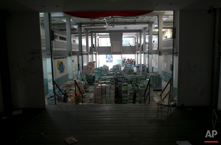 In this May 31, 2016 photo, a pile of 30,000 unopened textbooks block the auditorium stage, a favorite make-out spot for students at a public high school in Caracas, Venezuela. The government delivered the books at the start of the year, but teachers decided they were too full of pro-socialist propaganda to use. (AP Photo/Ariana Cubillos)