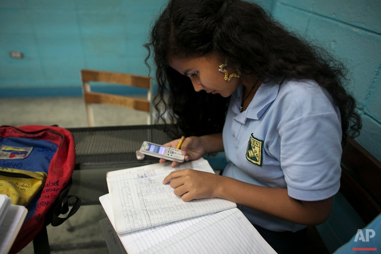 In this May 30, 2016 photo, Maria Arias, 14, quickly uses the calculator on a friend's cell phone to figure out why she has errors on her homework, during her accounting class at a public high school in Caracas, Venezuela. Arias' accounting teacher recently went missing for a week and a half, and when she showed up again, she limited herself to correcting homework. (AP Photo/Ariana Cubillos)