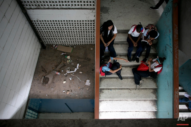In this June 1, 2016 photo, students sit on the stairs where trash fills one of the landings at their public high school in Caracas, Venezuela. The school looks less like a protected place of education than a downtown bus terminal; grimy, smelling of urine, and full of people waiting for teachers they're only half-sure will come. (AP Photo/Ariana Cubillos)