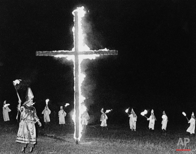 Hooded members of the United Klans of America in Mississippi wave flaming torches at an open-air torch burning near Edinburg in Central Mississippi, March 25, 1967. More than 3,000 Mississippians belonged to the United Klans at its peak in 1964, but now figures indicate there are fewer than 500 members, only 250 of whom pay dues. (AP Photo)